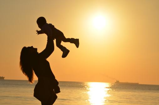 woman-carrying-baby-at-beach-during-sunset-51953