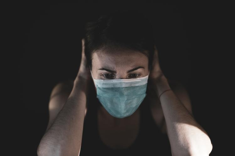 woman-covering-her-face-with-surgical-mask-4056228